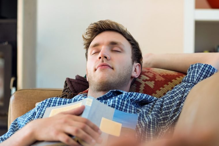 A man taking a nap while holding a book.