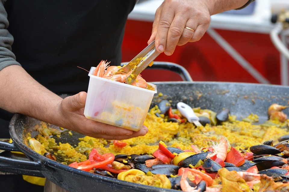 Paella with shells in a large pan.