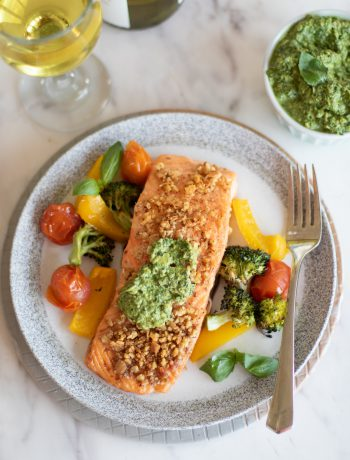 Pesto salmon with vegetables being served.