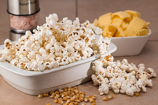 Popcorn in a bowl next to a bowl of chips.