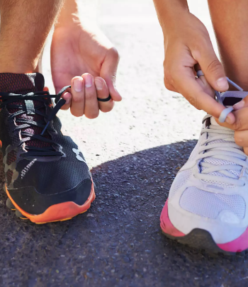 Man and woman tying their shoes preparing for a run.