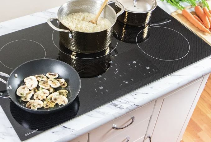 Rice and mushrooms cooking on an induction cooktop.