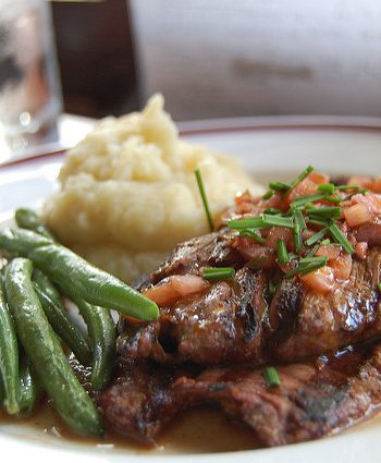 Skirt steak with mashed potatoes being served.