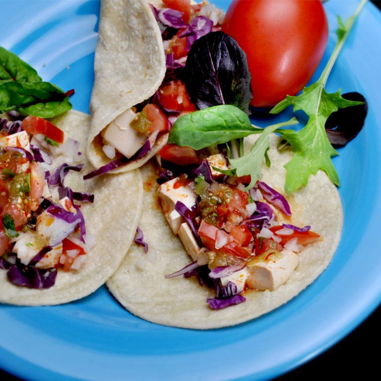 Tacos with onions and tomatoes on a plate.