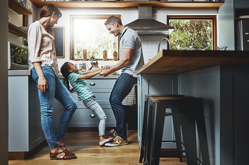 A family of three playing in a kitchen.
