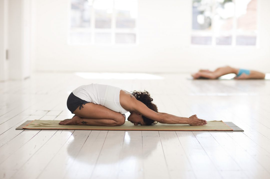 A woman practicing yoga in a room.