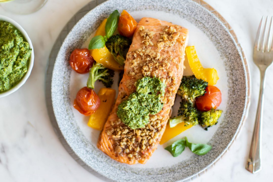 Baked Pesto Salmon and vegetables on a dish.
