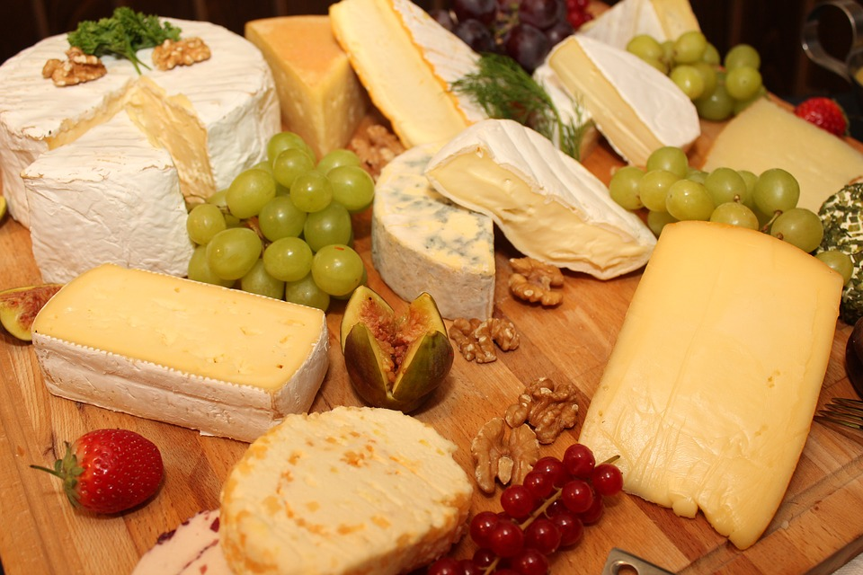 An array of cheese and grapes on a wood top.