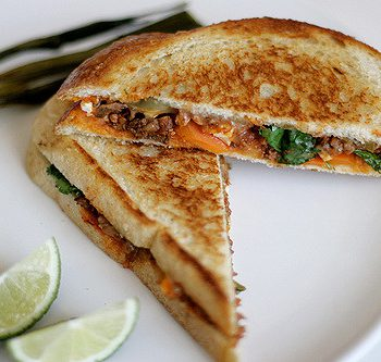 Grilled cheese and lime on a plate.