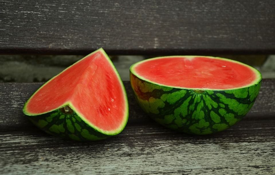 Watermellon chopped up on a bench.