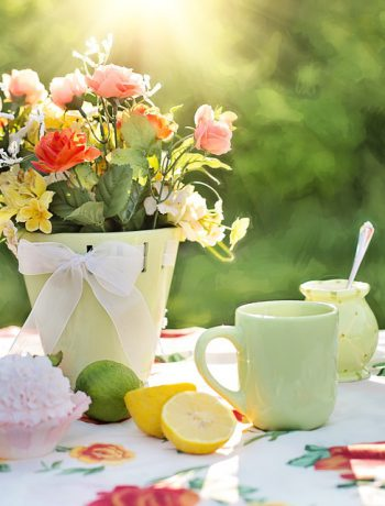Bouquet of flowers on an outdoor table with coffee cups and lemons.