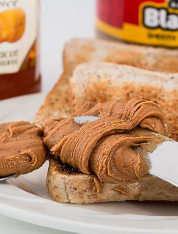 Peanut butter being smeared on a piece of bread.