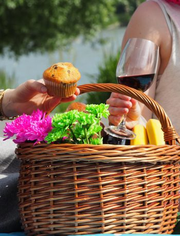 Picnic basket with flowers and foods including wine and muffins.