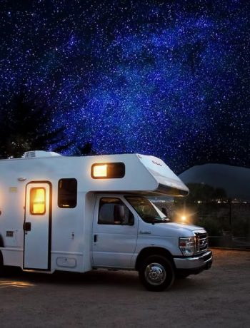 RV in a campsite woth starry sky in the background.