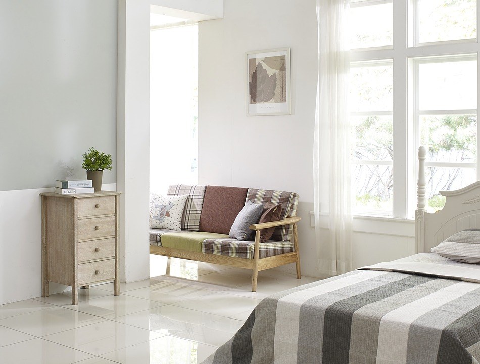 White bedroom design with light shining through the window,
