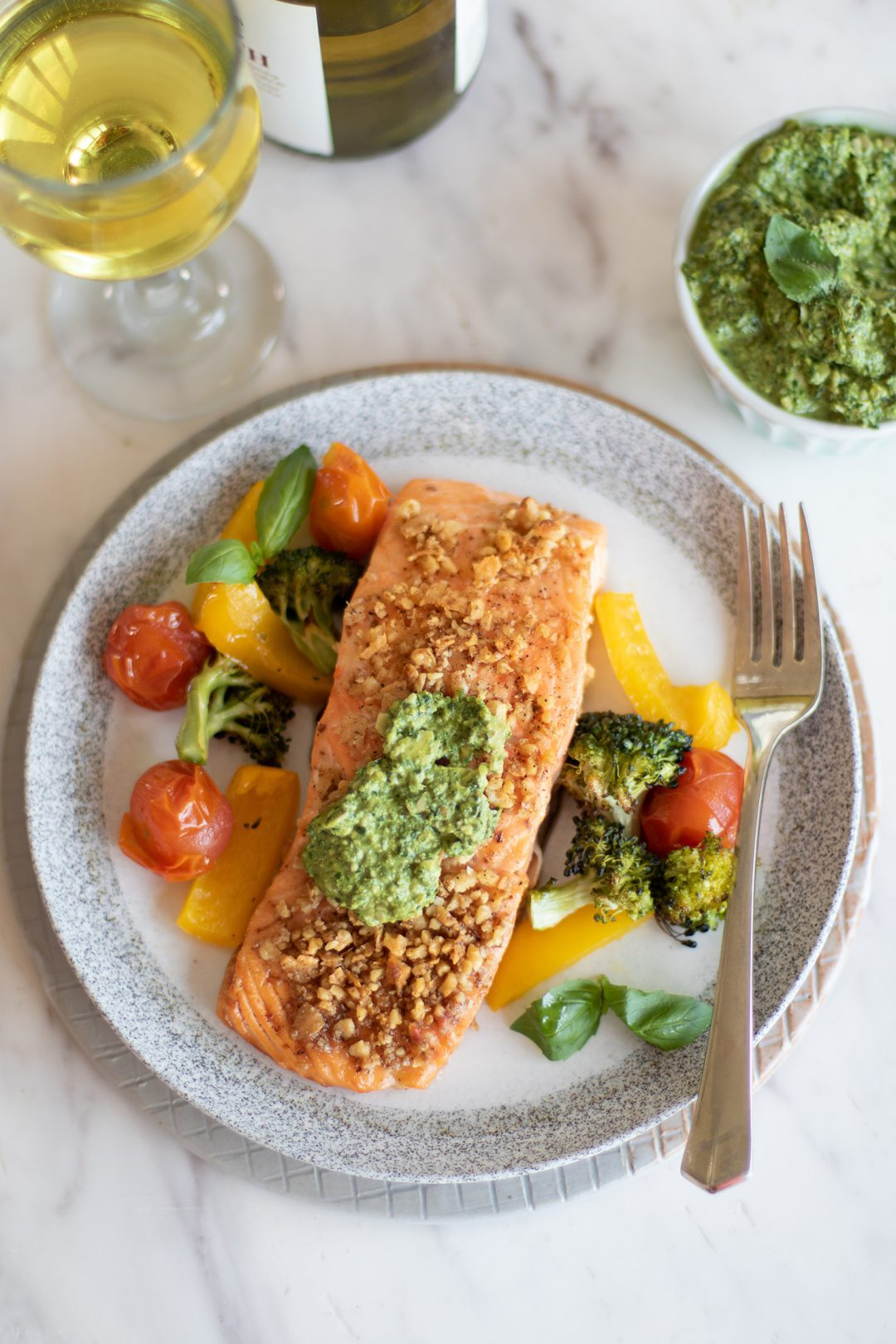 Baked Pesto Salmon on a plate next to a fork.