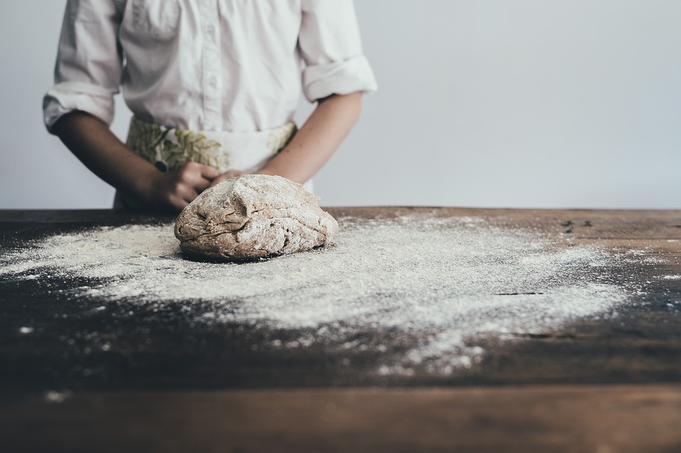 Dough on powder on a cutting board next to a chef.