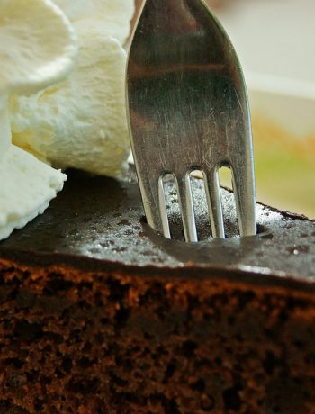 Fork pressing into chocolate cake with whipped cream.