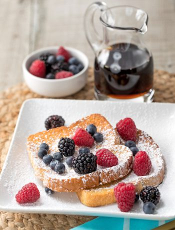 Toast on a plate with powder and rasberries next to syrup.