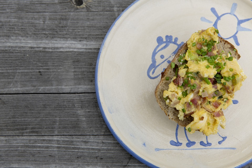 Loaded scrambled eggs on a plate on a wooden surface.