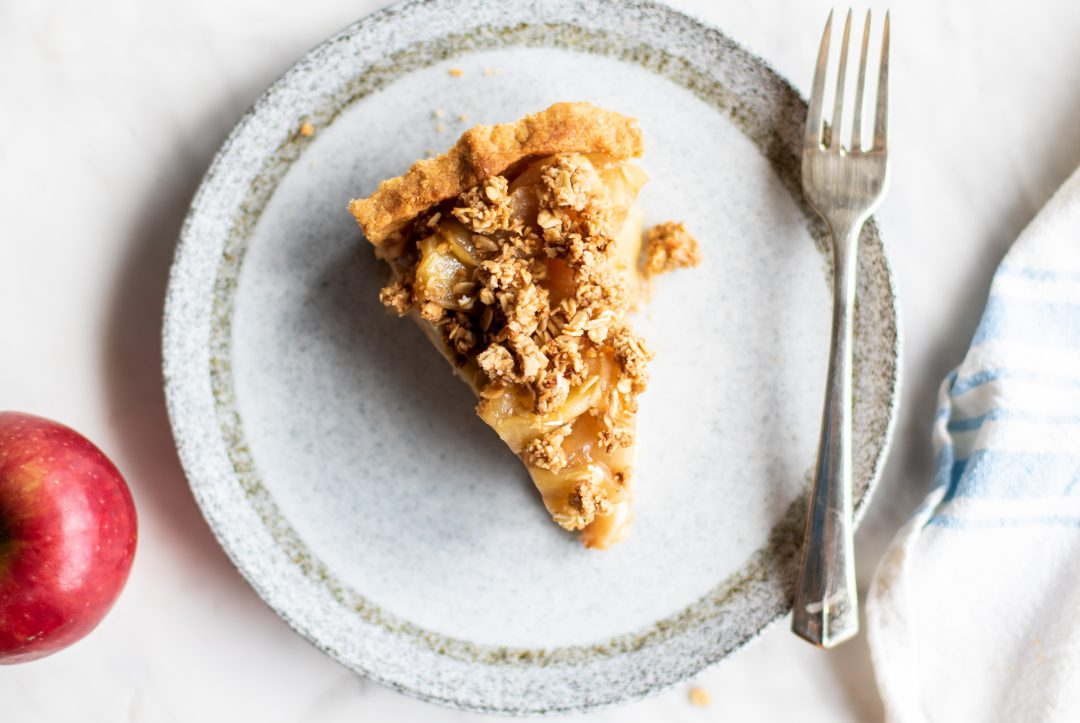 Apple pie on a plate next to a fork.