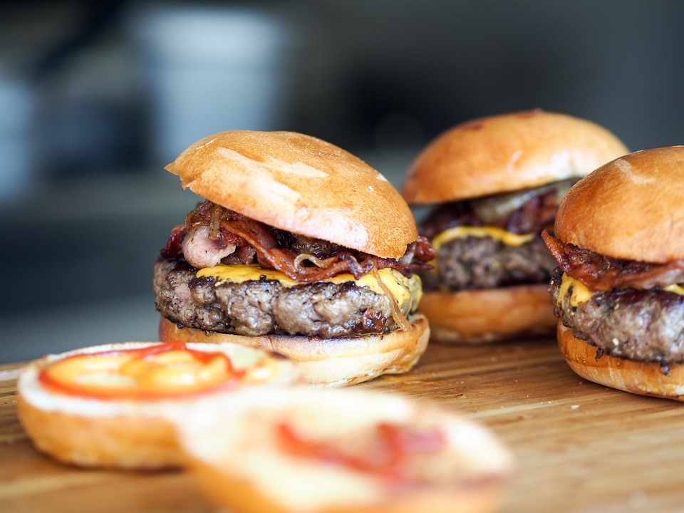 Three burgers on a wooden surface with tomatoe.