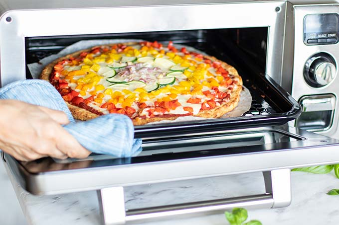 Pizza entering a Sharp Supersteam Oven.
