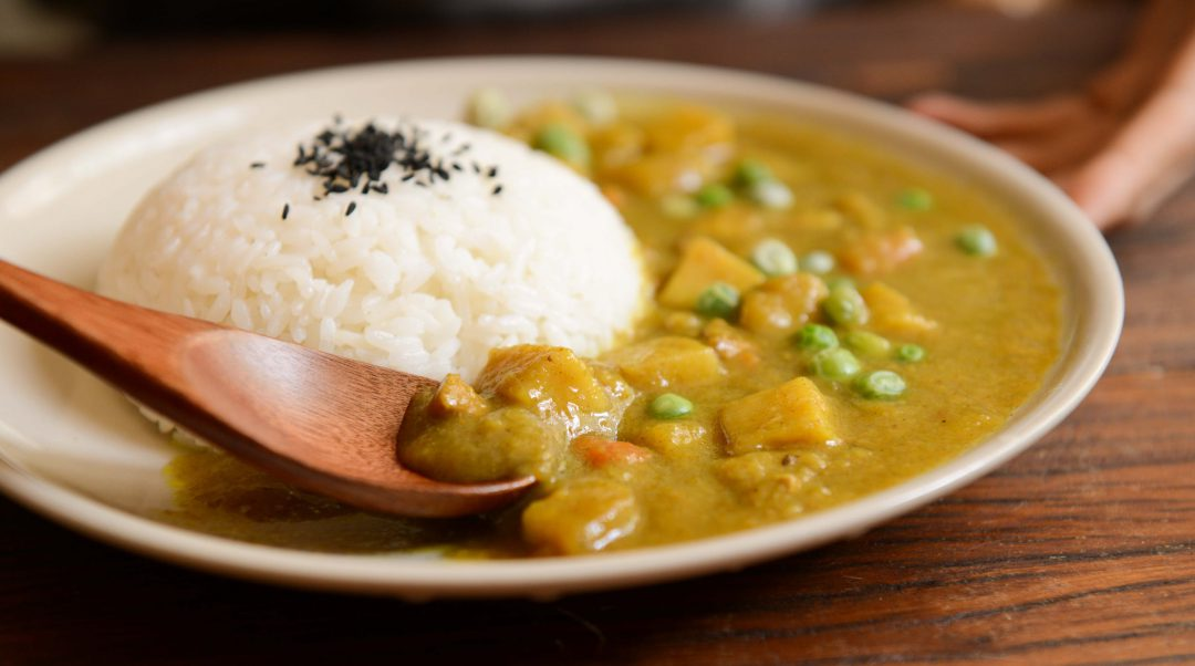Peanut Curry on a plate with a wooden spoon.