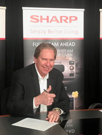 Peter Weedfald signing Nationwide contract with Sharp backdrop.