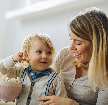 Smiling little boy and his mother eating popcorn.