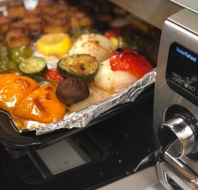 Sheetpan with vegetables entering a Sharp Supersteam Countertop Oven.