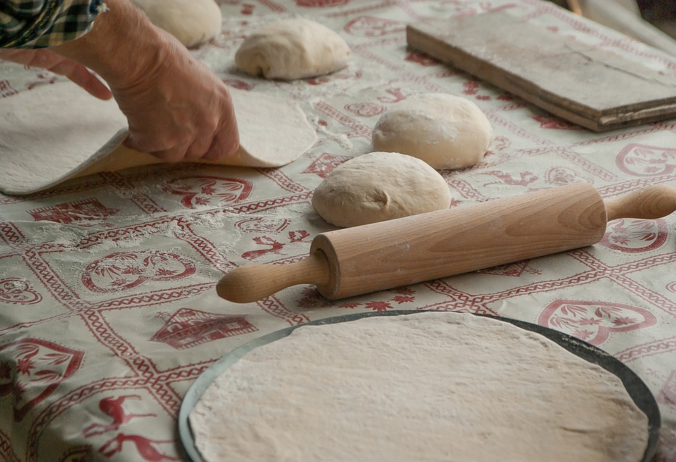 Pizza dough being rolled out on a table.