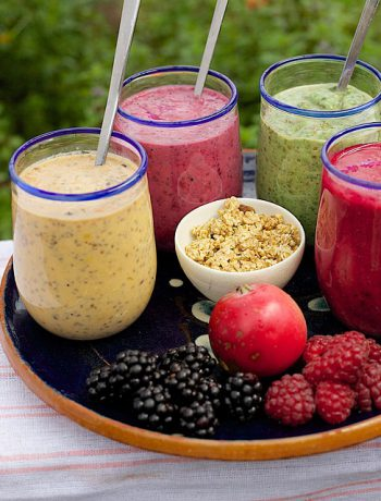 Four smoothie flavors with rasberries on an outdoor tray.