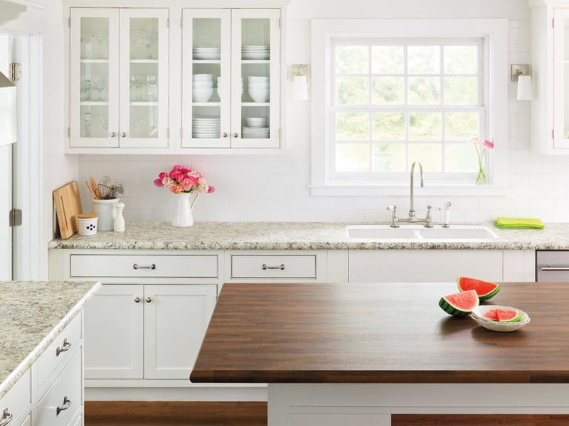 White classic kitchen design with wooden island.