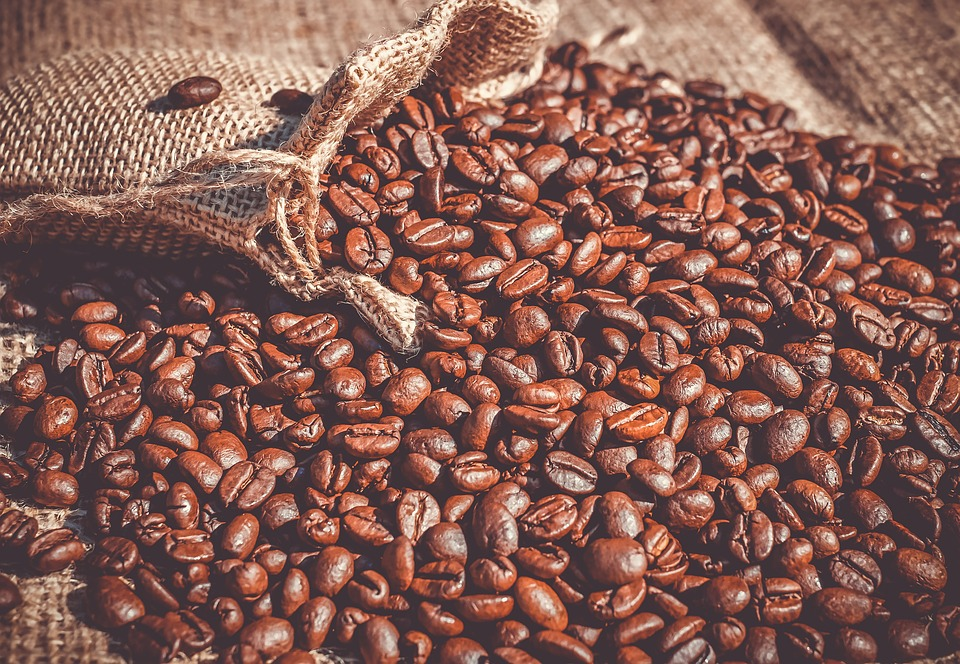 Coffee beans in sack spread across a table.