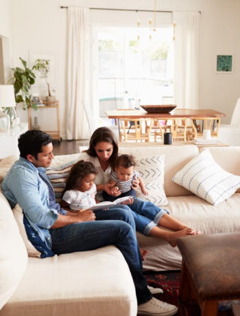 Family of four sitting in a living room with young children.