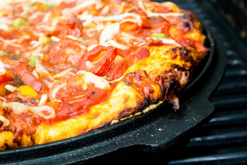 Gluten free deep dish pizza on a grille.