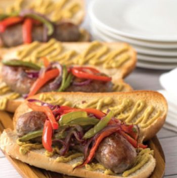 Grilled brats on a wooden surface with plates and napkins.