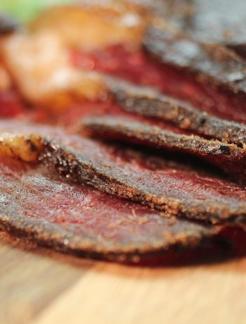 Homemade Beef Jerky on a wooden surface.
