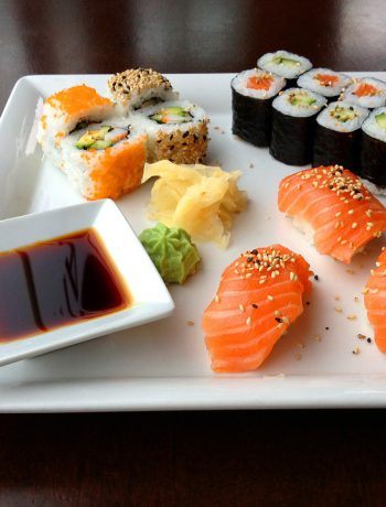 Sushi on a white square plate with sauce.