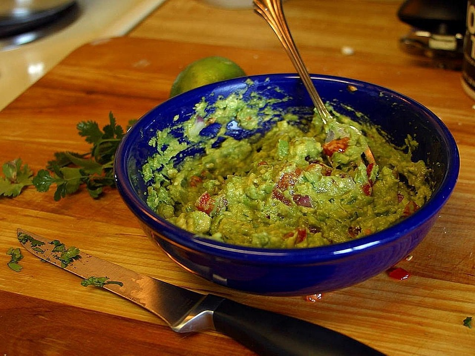 Blue bowl filled with guac and a spoon on a wooden surface.