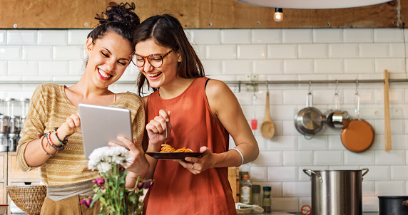 Two femail friends looking at a tablet in a kitchen.