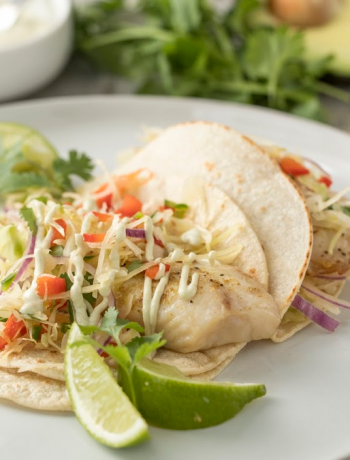 Fish tacos on a plate with lime.