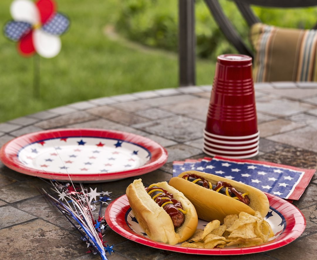 Two hot dogs with ketchup and mustard on a plate with cups at a barbeque setting.