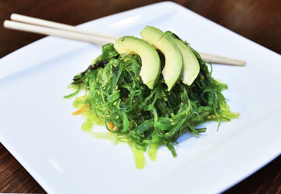 Seaweed Salad on a white plate with chopsticks.