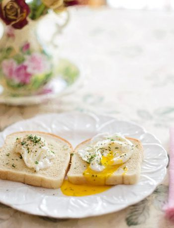Two pieces of toast with eggs at a bruch setting.