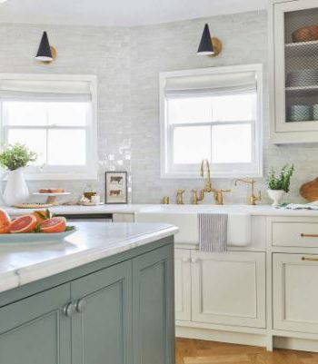 White kitchen design with a blue island and gold hardware.
