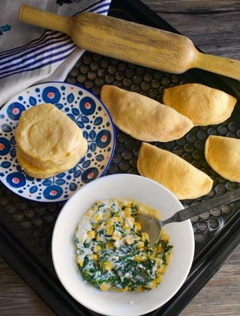Ricotta Spinach and Corn Empanadas on a tray next to a blue cloth.