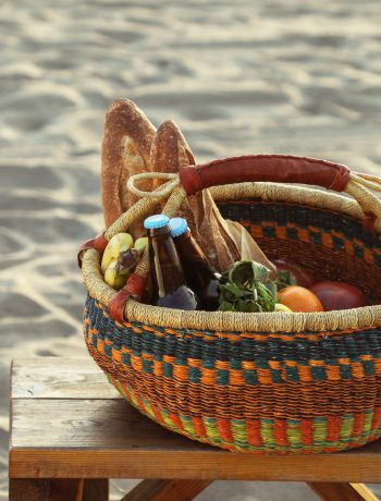 Basket of food and drinks on a wooden table on a sanded beach.