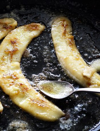 Bananas cooking in a pan next to a spoon.